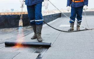 Two workers use a blowtorch to apply modified bitumen.