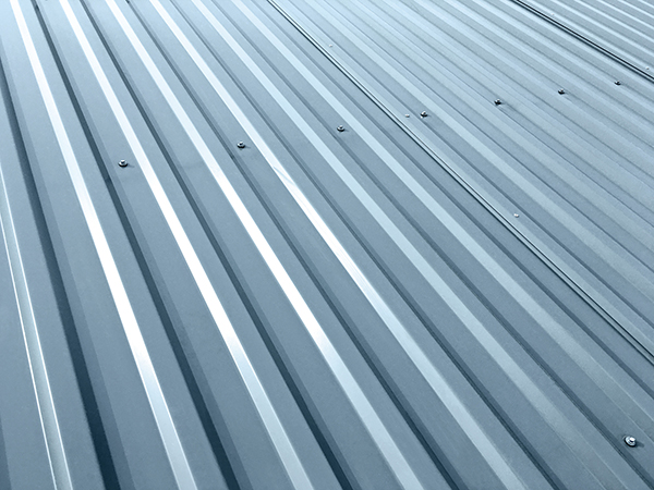 Corrugated gray metal sheets with rivets on roof of an industrial building