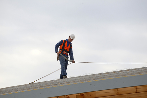 A builder secures safety lines for men about to climb on a large flat commercial roof.