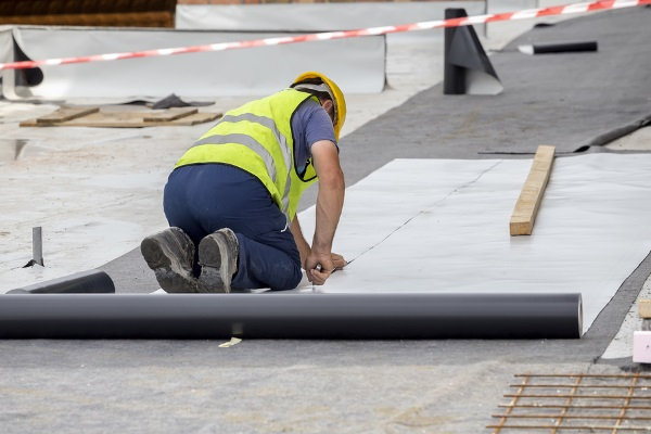 roofers installing asphalt rolled roofs